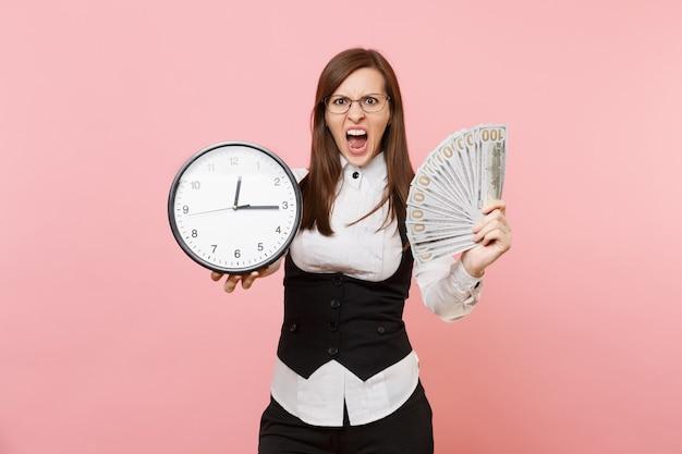 眼鏡の悲鳴を上げる若いイライラしたビジネス女性は、ピンクの背景に分離されたたくさんのドルの現金と目覚まし時計のバンドルを保持します。女上司。達成キャリアの富。広告用のスペースをコピーします。