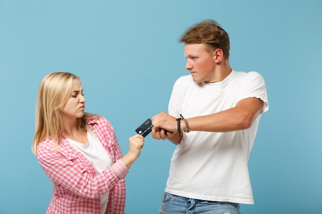 Young irritated couple two friends guy and woman in white pink empty blank t-shirts posing