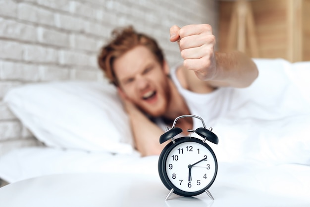 Young irritated man reaches out to turn off alarm clock.