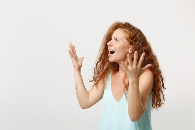 Giovane donna rossa perplessa irritata in vestiti leggeri casuali che posano isolato sul fondo bianco della parete. concetto di stile di vita di emozioni sincere della gente. mock up copia spazio. guardando da parte, allargando le mani.
