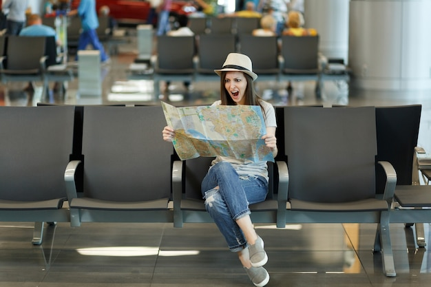 Young irritated traveler tourist woman holding paper map, searching route, screaming waiting in lobby hall at airport