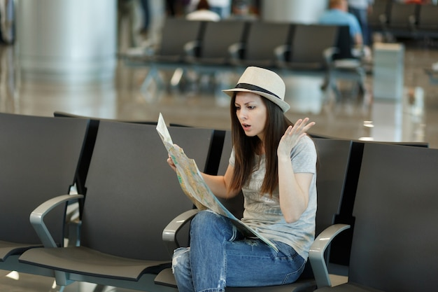 紙の地図を持って、ルートを検索し、手を広げ、空港のロビーホールで待つ若いイライラした旅行者観光客の女性