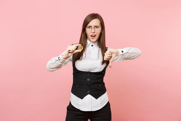 안경을 쓴 젊은 화가 난 비즈니스 여성은 비트코인을 들고 파스텔 핑크색 배경에 고립되어 엄지손가락을 아래로 내밀었습니다. 여사장님. 성취 경력 부 개념입니다. 광고 공간을 복사합니다.