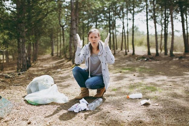 평상복을 입은 젊은 짜증난 여성과 장갑을 끼고 쓰레기를 청소하고 공원의 쓰레기 봉투 근처에 손을 펼칩니다. 환경 오염 문제