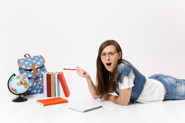 Young irritated woman student in denim clothes, glasses writing notes on notebook and lying near globe, backpack, school book isolated