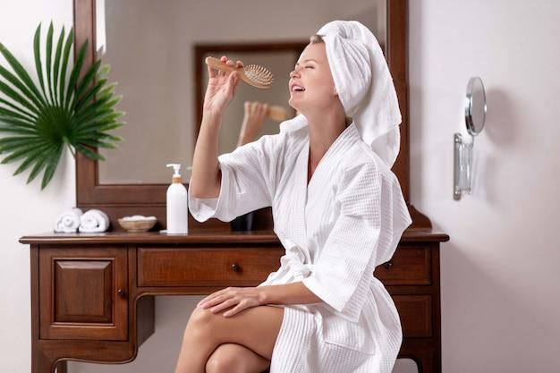 Юная красавица в вафельном халате и полотенце на голове позирует сидя на стуле возле туалетного столика, на котором лежат махровые полотенца, ватные подушечки в корзине. пение в деревянной расческе.