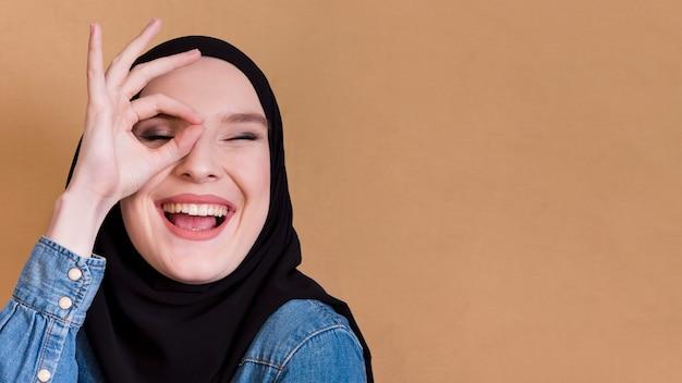 Young islamic joyful female holding fingers in ok gesture over her eye