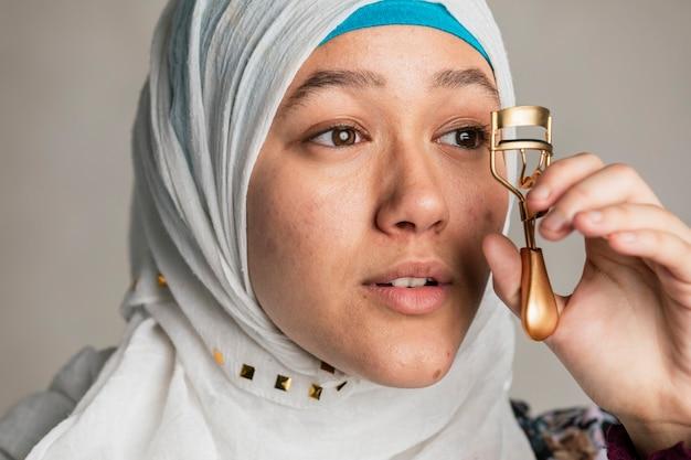 彼女のまつげをカールする若いイスラムの女性