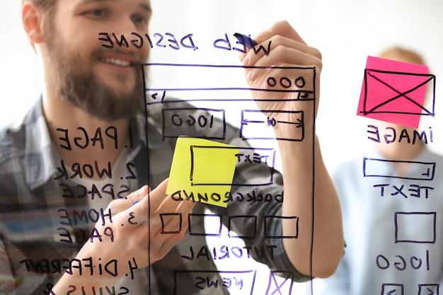 프로젝트를 논의하는 젊은 it 디자이너, 투명 게시판을 통해보기
