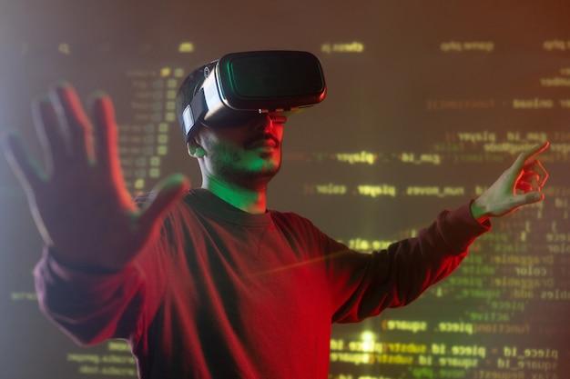 Молодой ит-менеджер с vr-гарнитурой стоит перед большим виртуальным дисплеем и демонстрирует расшифрованную информацию
