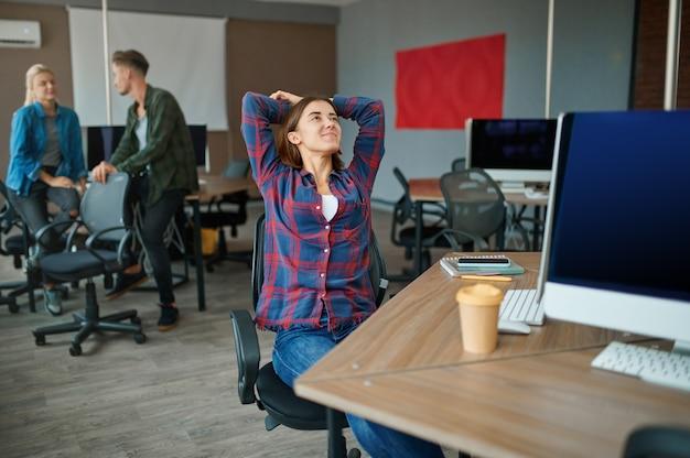Молодые айтишники приветствуют друг друга в офисе. веб-программист или дизайнер на рабочем месте, творческое занятие. современные информационные технологии, корпоративный коллектив