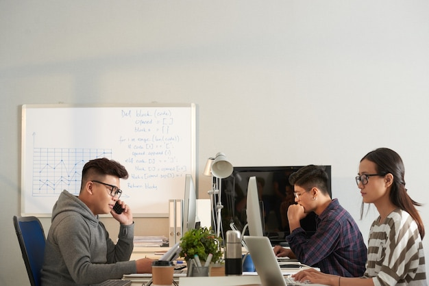 Young it specialists working on computers in modern office with big whiteboard