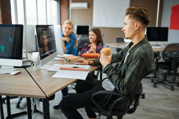 Young it specialists works on computers in office. web programmer or designer at workplace, creative occupation. modern information technology, corporate team