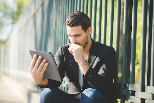 Young italian boy seated on a sidewalk using tablet