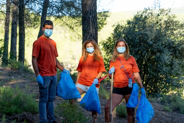 Young janitors working in the woods collecting garbage.