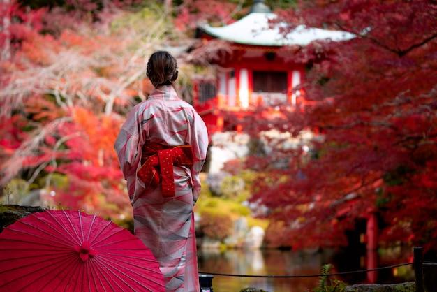 Молодая японская путешественница в традиционном платье кимино стоит в храме дигодзи