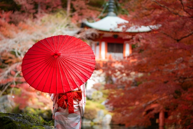 Young japanese girl traveller in traditional kimino dress standing in digoji temple with red pagoda and red maple leaf in autumn season in kyoto, japan.