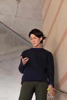 Giovane giapponese con un maglione blu all'aperto