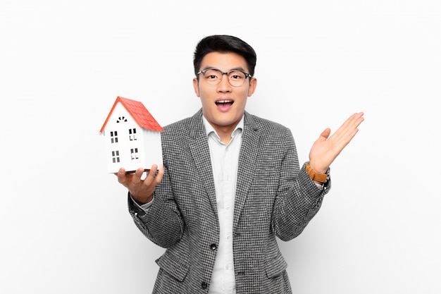 Молодой японец чувствует себя счастливым, взволнованным, удивленным или шокированным, улыбается и удивлен чему-то невероятному с моделью дома