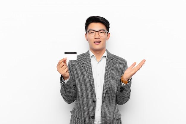 幸せ、驚き、陽気、前向きな姿勢で笑って、解決策やアイデアを実現する日本の若い男。クレジットカードの概念。