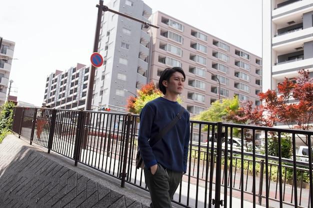 街の青いセーターを着た若い日本人男性