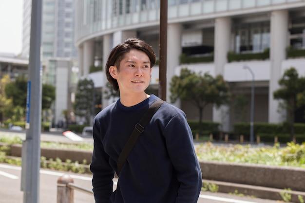 屋外で青いセーターを着た若い日本人男性