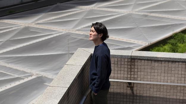 青いセーターを着た若い日本人男性