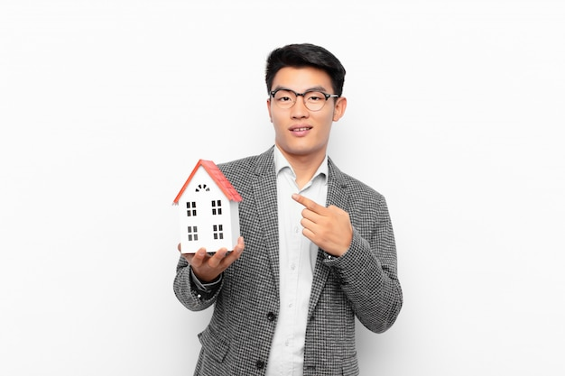 Молодой японец выглядит взволнованным и удивленным, указывая в сторону и вверх, чтобы скопировать пространство с моделью дома
