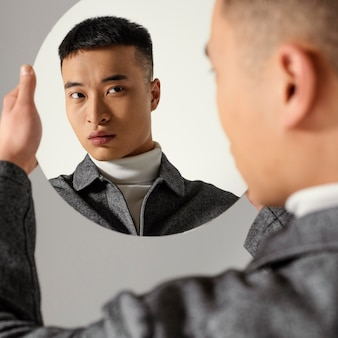 Young japanese man portrait looking in mirror