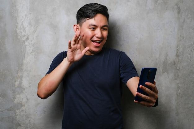 콘크리트 벽 배경에서 스마트폰으로 화상 통화를 하며 행복한 미소를 짓고 있는 일본 청년