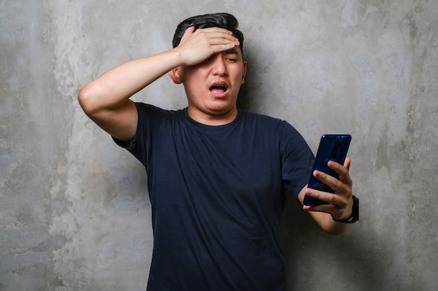 スマートフォンを使用している若い日本人男性は、頭に手を当ててストレスを感じ、恥と驚きの顔にショックを受け、コンクリートの壁の背景に怒りと欲求不満を感じました。間違いに対する恐れと動揺。