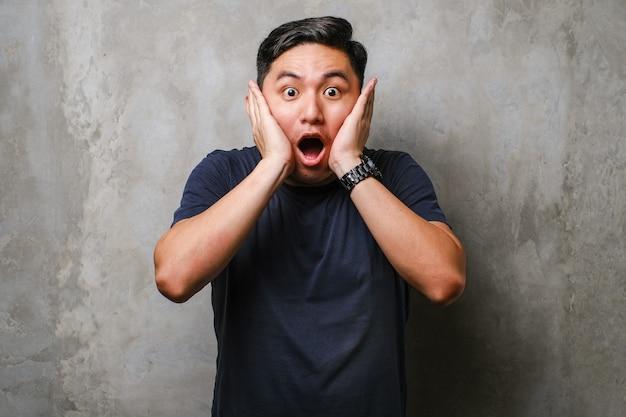 Молодой японец в футболке стоит на фоне бетонной стены, испуганный и шокированный, удивленный и удивленный с руками на лице