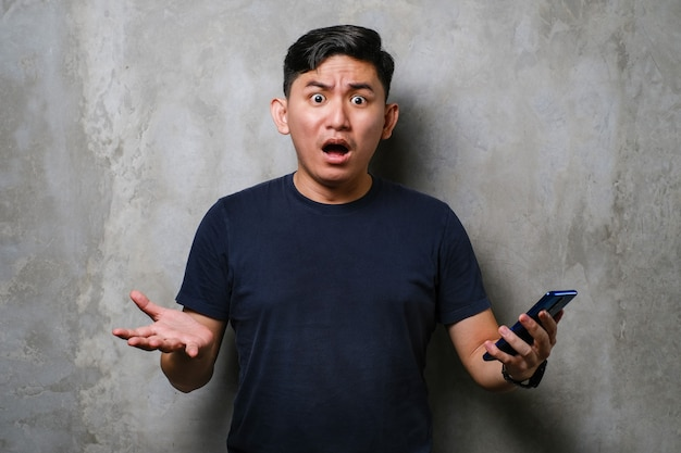 Young japanese man wearing tshirt using smartphone clueless and confused expression over concrete wall background. doubt concept.