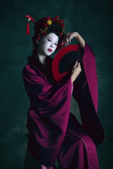 Young japanese woman as geisha on dark green background retro style comparison of eras concept