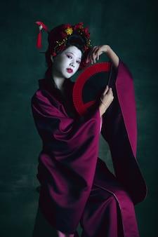 Молодая японка в роли гейши на темно-зеленом фоне в стиле ретро, сравнение концепции эпох