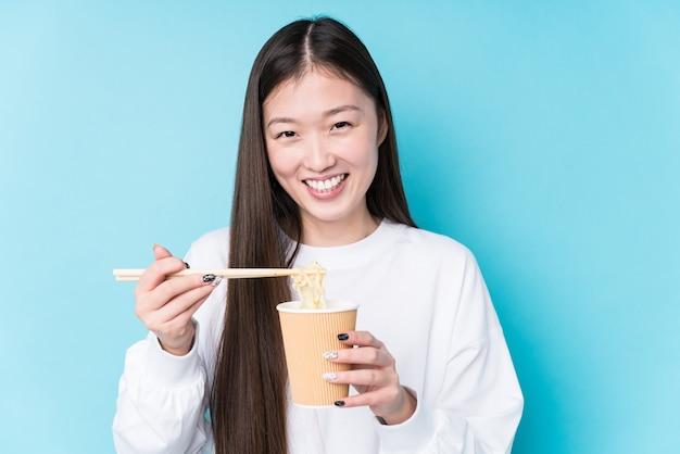 Молодая японская женщина ест лапшу