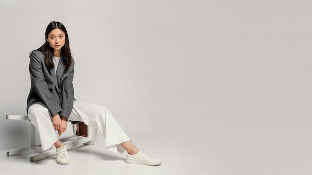 Портрет молодой японской женщины, сидя на стуле