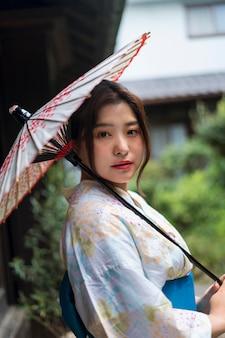 Giovane donna giapponese che indossa un kimono e tiene un ombrello
