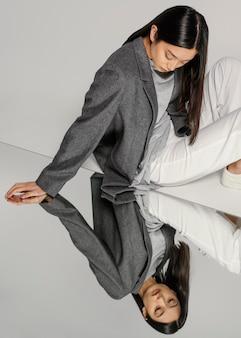 Giovane donna giapponese con giacca in posa nello specchio
