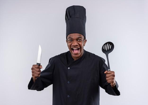 シェフの制服を着た若い楽しいアフリカ系アメリカ人の料理人は、白い壁に隔離されたナイフとヘラを保持します