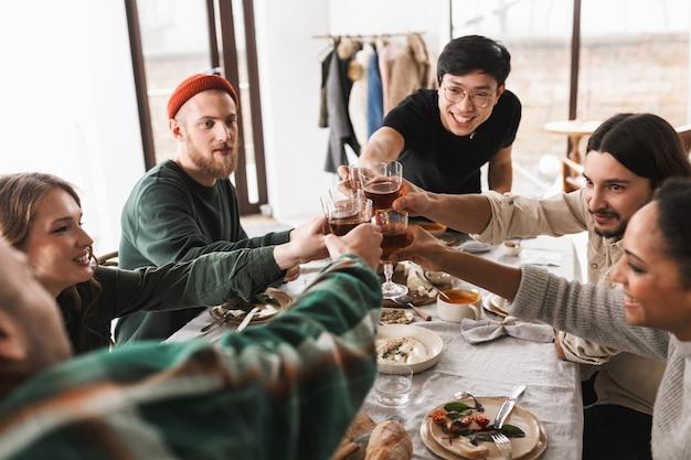 Молодой радостный азиатский мужчина в очках и черной футболке радостно приветствует бокалы вина с коллегами
