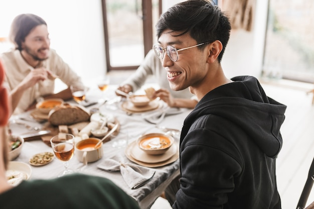 Young joyful asian man with dark hair in eyeglasses and hoodie sitting at the table happily