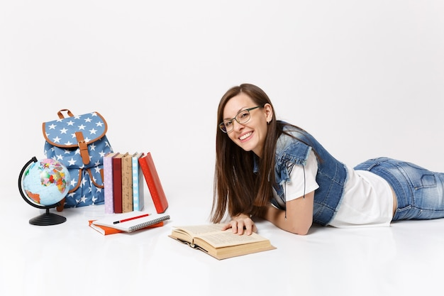 Giovane studentessa allegra e attraente in abiti denim, occhiali da lettura libro sdraiato vicino al globo, zaino, libri scolastici isolati