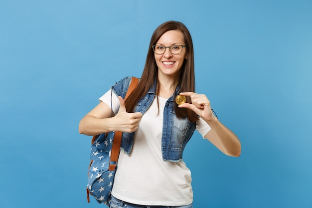 Young joyful attractive woman student in glasses showing thumb up holding bitcoin, metal coin of golden color isolated on blue background. future currency. education in high school university college.