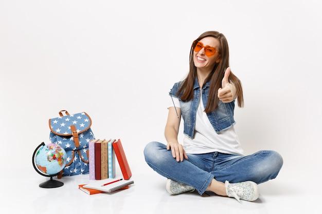 Giovane studentessa allegra e attraente con gli occhiali a cuore rosso che mostra il pollice seduto vicino ai libri di scuola dello zaino del globo