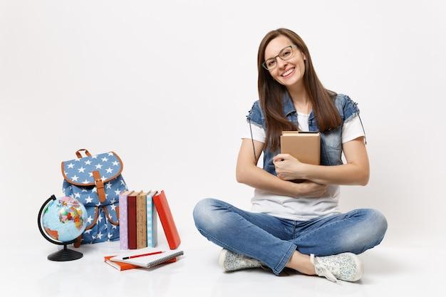 Giovane bella studentessa gioiosa con gli occhiali in denim che tiene in mano un libro seduto vicino al globo, zaino, libri scolastici isolati