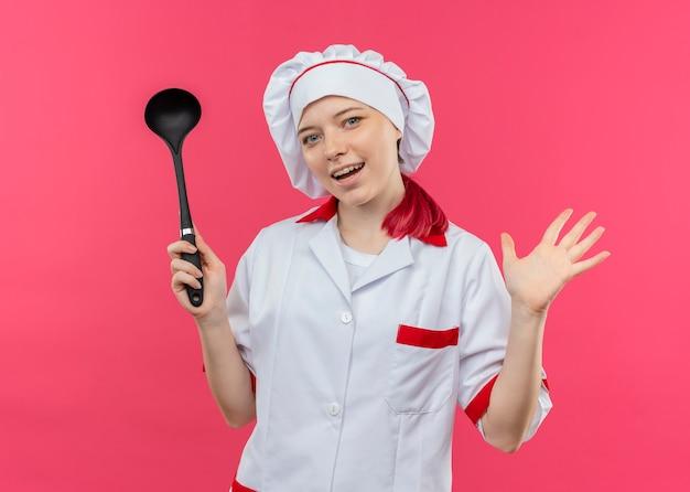 Молодая радостная блондинка-шеф-повар в форме шеф-повара держит ковш и держит руку открытой, изолированную на розовой стене