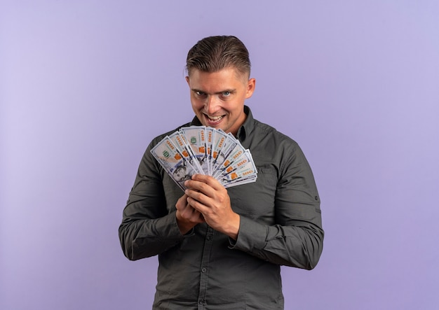 Young joyful blonde handsome man holds money and looks at camera isolated on violet space with copy space