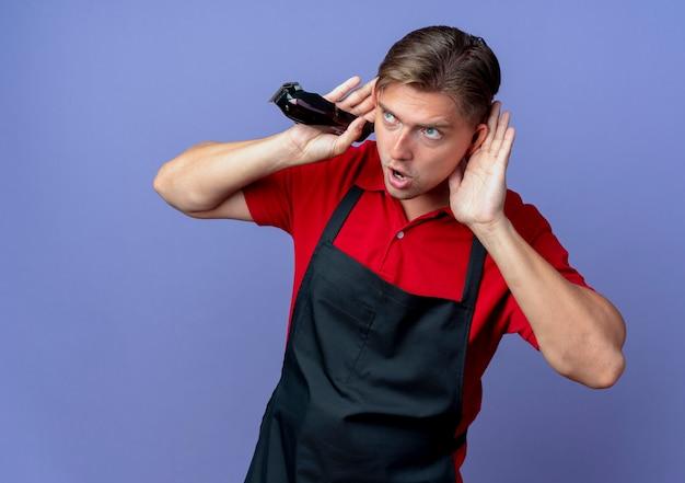 Giovane barbiere maschio biondo gioioso in uniforme mette le mani dietro le orecchie guardando il tagliatore di capelli della holding del lato isolato sullo spazio viola con lo spazio della copia