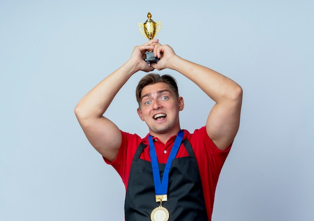 Young joyful blonde male barber in uniform with gold medal around neck holds winner cup over head isolated on white space with copy space